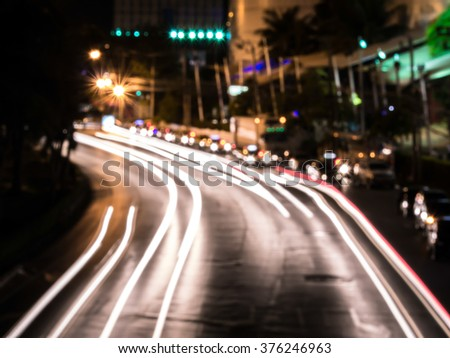Abstract blur moving car with blur light through city at night - stock photo