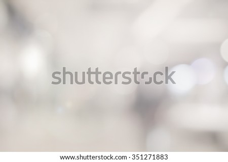abstract blur of grey/sepia gradient color toned colored of store mall background:blurry brighten backdrop with shiny lens flare lights:blur soft silver color wallpaper.horizon display picture concept - stock photo