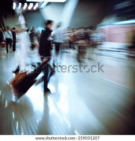 abstract blur of passengers rushing at big city station. - stock photo
