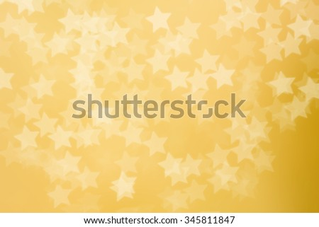 abstract blur of star lights over golden yellow backdrop:blur Christmas festival decorations backgrounds with star shining lights:blur wallpaper concept.xmas celebration decorate texture. - stock photo