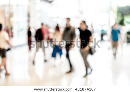 Abstract blur people walking in fashion mall. Strong light coming from outside - stock photo