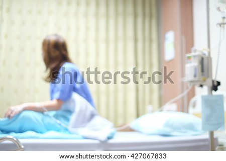 abstract blurred asian woman patient sickness sitting on bed at hospital:health care medical concept.young girl are rehabilitate after surgery operate medical to improve her cancer disease symptoms. - stock photo