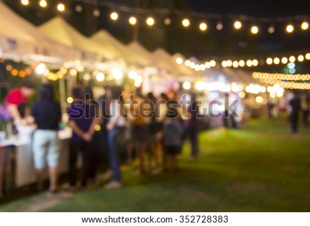 Abstract blurred background of people shopping at night festival - stock photo