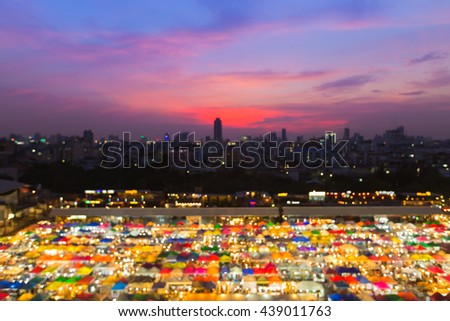 Abstract blurred bokeh lights aerial view night market roof top, multiple colours background - stock photo