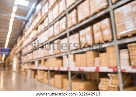 Abstract blurred boxes on rows of shelves in big modern warehouse background - stock photo
