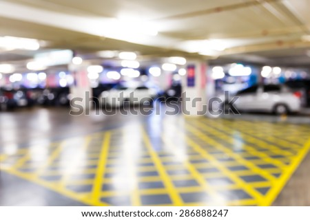 Abstract blurred car in parking lot of office building - stock photo