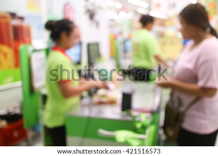 abstract blurred cashier at a supermarket checkout in a department store. - stock photo