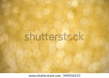 abstract blurred glitter golden background:blur motion bulbs light in gold colored backdrop wallpaper.xmas background concept. - stock photo