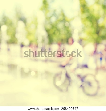 Abstract blurred image of man on bicycle in the city. - stock photo