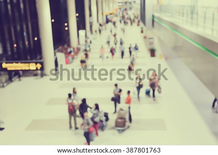 abstract blurred of movement crowd people walking to the airport gate for travel or business:blur of indoor architecture concept:blurry people walking crowded conception.traveler concept.vintage tone. - stock photo