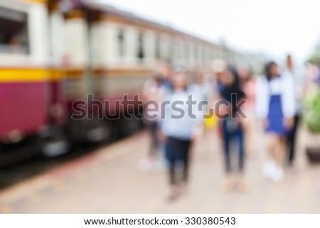 Abstract blurred people at old style train station, rural travelling concept - stock photo