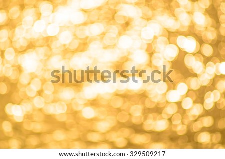 Abstract blurred yellow bright sepia background with sun reflection on the water. True bokeh. - stock photo