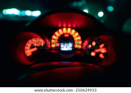 Abstract bokeh of car speed meter light dashboard with traffic  light at night - stock photo