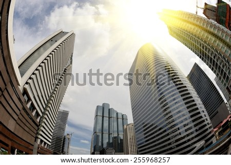 Abstract business background with office building and Sunbeam on sky, shot with a Fisheye lens. - stock photo