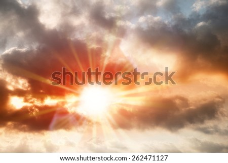 Abstract busy dark cloud over vibrant color sky with red sunstar flare background - stock photo