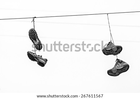 abstract composition from two couples fragmentary sneakers which hang highly on wires on a background of the sky of monochrome tone - stock photo
