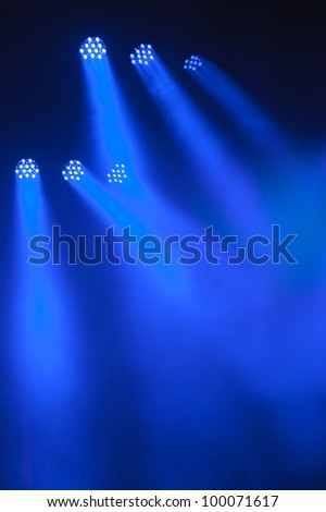 Abstract dark background with bright blue stage spotlights - stock photo