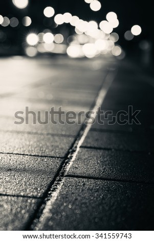 Abstract dark blurry background. Wet pavement tiles. Shallow depth of field. - stock photo