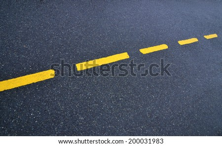 Abstract detail of asphalt road with yellow strip - stock photo