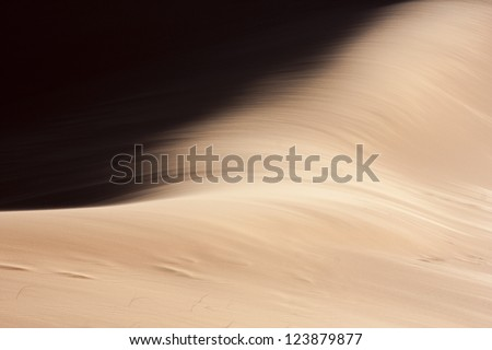 Abstract detail of sand hit by wind in the dunes of Eastern Sahara - stock photo