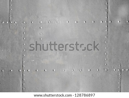 Abstract detailed gray metal wall background texture with seams and rivets - stock photo