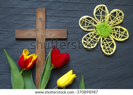 Abstract easter tulips and wooden cross on black marble - stock photo