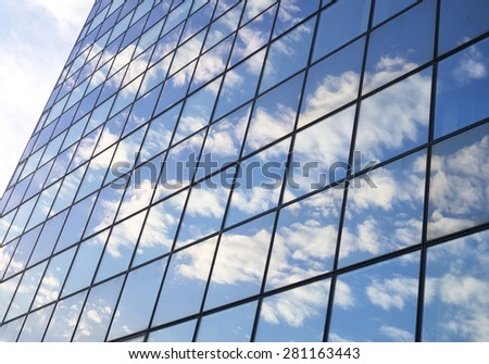 Abstract facade of a modern office building with reflecting clouds - stock photo
