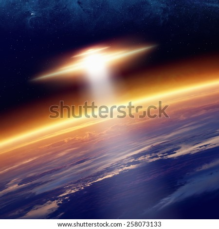 Abstract fantastic background - ufo with bright spotlight approaches glowing planet Earth in space. Elements of this image furnished by NASA  - stock photo