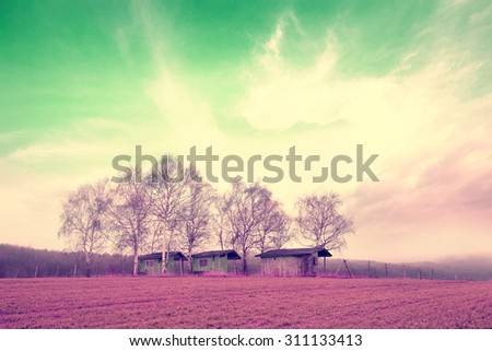 abstract filtered infrared landscape with barns in farmland - stock photo