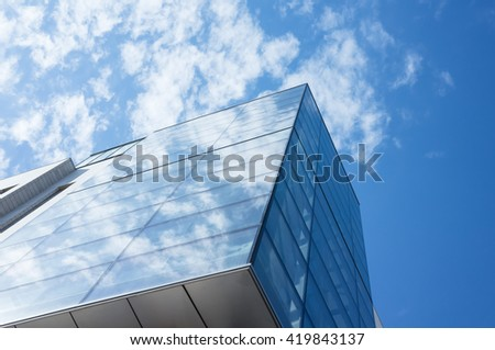 Abstract fragment of modern architecture, walls made of glass and steel. Blue cloudy sky reflections - stock photo