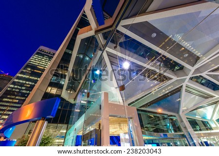 Abstract. Fragment of the modern company, office, shopping centre, mall building of the colorful city with skyscrapers, highrise buildings. Vancouver downtown  at night. - stock photo