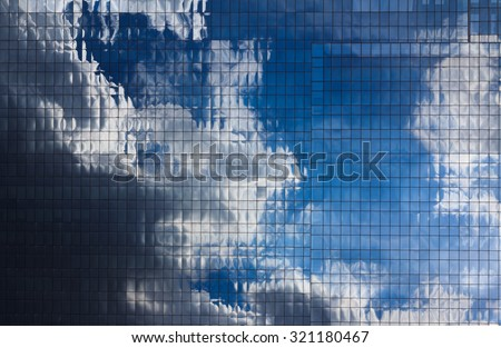 Abstract Glass Building reflection daylight as blue sky background - stock photo
