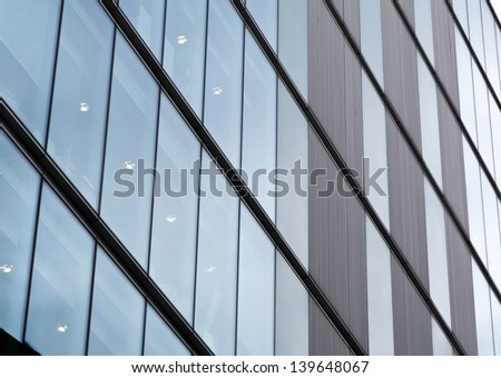 Abstract glass wall of office block; impersonal facade of city office block  - stock photo