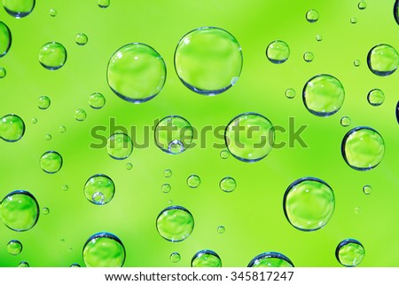 Abstract green background with various water drops - stock photo