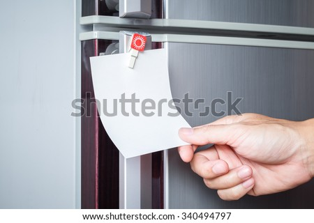 Abstract hand catch empty paper sheet on refrigerator door - stock photo