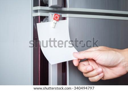 Abstract hand catch empty paper sheet on refrigerator door - stock photo
