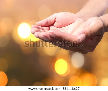 abstract Hand with a golden background bokeh. Pray for Christians. Prayer to bless our world. The Society of the Capital - stock photo