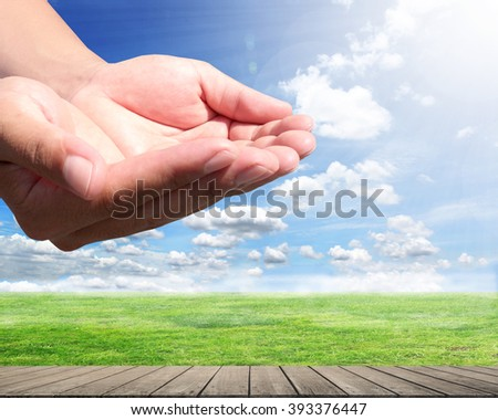 Abstract hand with meadows in the background. Blessings from heaven. The abundance of world. Love the holidays. hand Earth sky Meadow wooden balcony - stock photo