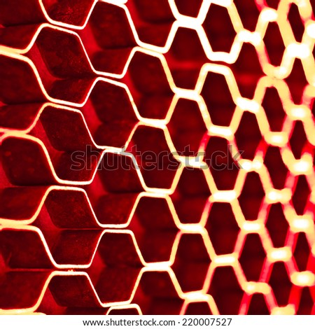 Abstract hexagonal structure with shallow dof. Red metal honeycomb mesh. Technology concept. - stock photo