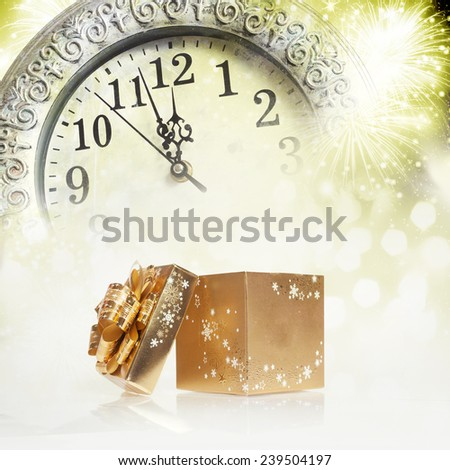 abstract holiday background with golden gift box, clock close to midnight and fireworks  - stock photo