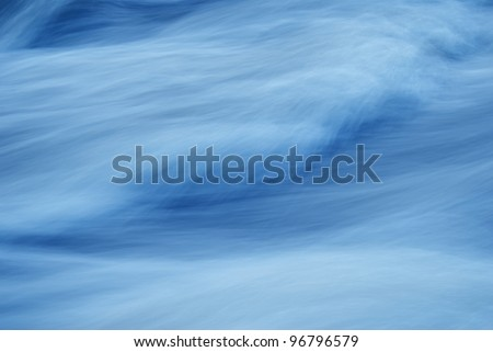 Abstract image of a swiftly moving stream in shades of blue. - stock photo