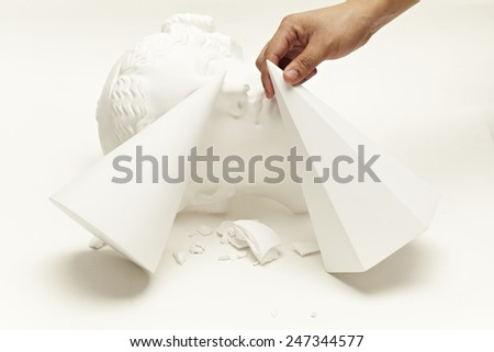 abstract image of head sculpture and human hand - stock photo