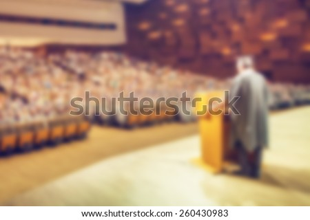 Abstract image of student holding valedictorian speech at graduation ceremony. Intentionally blurred in post processing. - stock photo