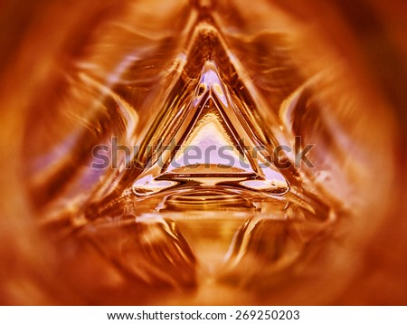 Abstract image of the inside of a triangle glass bottle orange color background - stock photo