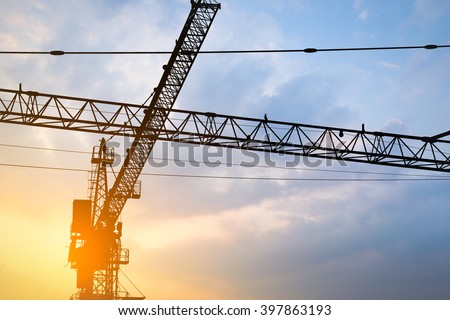 Abstract Industrial background with construction cranes silhouettes over amazing sunset sky - stock photo