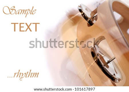 Abstract macro image of tambourine being shaken on white background with copy space.  Intentional motion blur captured with movement during exposure to create effect. - stock photo