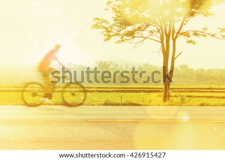abstract man riding bicycles on a road ,Intentional motion blur - stock photo