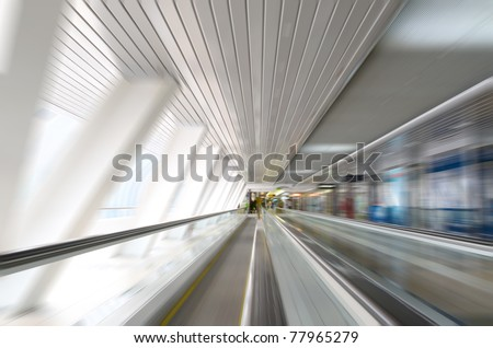 Abstract motion in corridor with escalators - stock photo