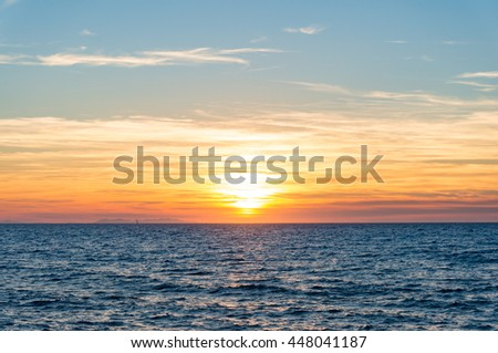Abstract nature background of colorful sunset sky and calm sea with distant view of Corsica. Italy - stock photo