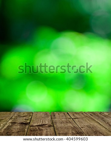 abstract nature background with wood floor. Wooden floor perspective and green forest with ray of light. - stock photo